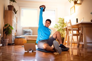 man doing a learning how to do a turkish get-up exercise on a tablet in his living room