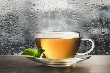 Glass cup of hot green tea near window on rainy day