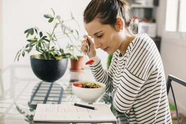 Woman sitting at table with her brain breakfast of overnight oats with blueberries and walnuts looking at notepad