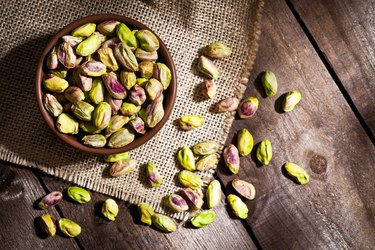 CoQ10-rich pistachios in bowl on wooden table