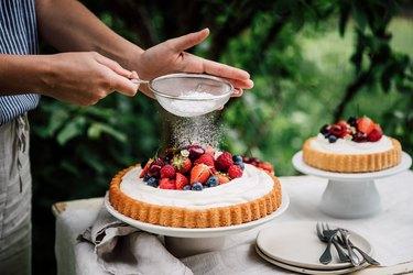 Woman preparing fresh fruits and berries cake with gluten-free sugar
