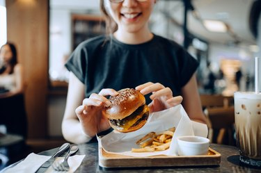 woman eating a burger and fries, as an example of foods to avoid with GERD