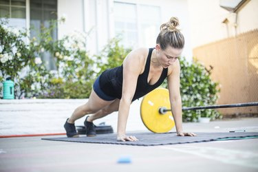caucasian woman in black tank and shorts doing push-ups on a black yoga mat outside her home, feeling pain from push-ups