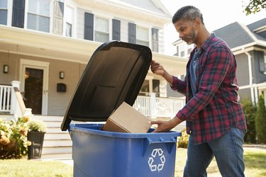 man filling recycling bin on suburban street avoiding common recycling mistakes