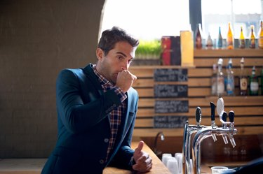 A man burping while standing at a bar
