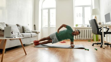 Man doing a side plank during morning workout at home