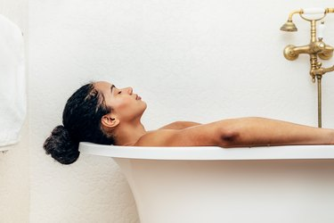 Side view of young woman taking a bath, as a natural remedy for sunburns