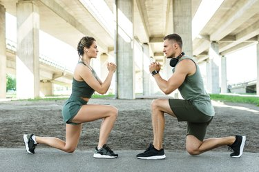 athletic man and woman lunging forward outside