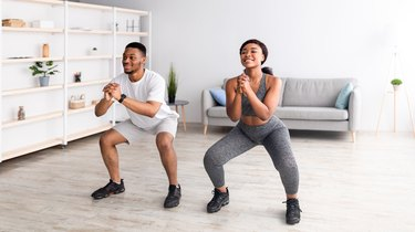 Fit black couple doing air squats, a beginner glute exercise, together in their living room