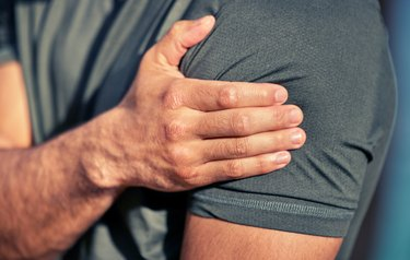 closeup shot of a man holding his shoulder, considering if he can do a strength workout after a flu shot