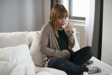 Young woman sick in bed holding glass of water.