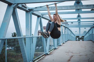 Woman doing hanging knee tucks outdoors on a bridge