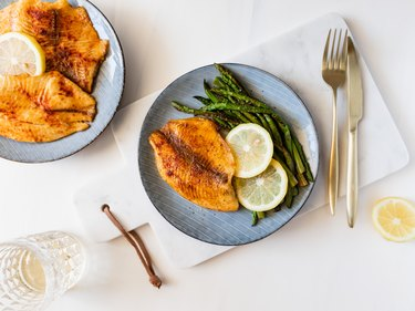 Roasted tilapia fish with asparagus on a ceramic plate. Healthy mediterranean diet lunch or dinner. Top view, flat lay.