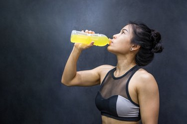 Athlete drinking sport drink or energy drink after exercise