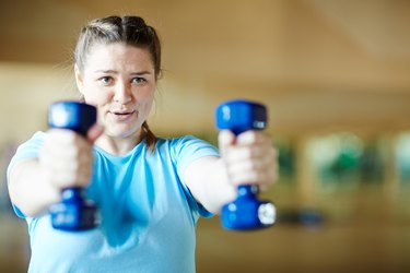 Woman doing front raises during a workout with dumbbells