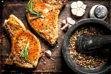 Tyrosine-rich grilled lean pork chops with spices and garlic on a wooden board.