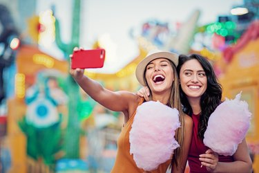 Happy girlfriends are taking selfie/making video call and make fun together in a fun fair