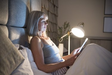 Woman sitting upright in bed, as a natural remedy for nausea