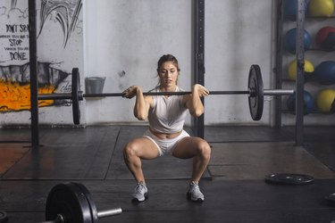 woman doing a barbell front squat at the gym
