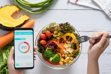 view of a person eating salad and using a calorie counting app, to demonstrate following a very low calorie diet