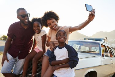 Family Posing For Selfie Next To Car Packed For Road Trip during COVID pandemic
