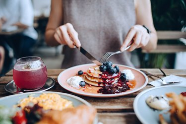 Close up of young woman sitting at dining table eating pancakes with blueberries and whipped cream in cafe