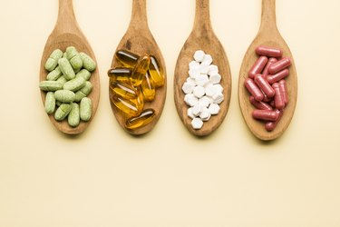 overhead photo of four types of supplement and vitamin pills in wooden spoons
