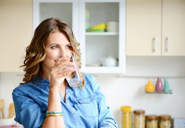 woman in the kitchen drinking a glass of water
