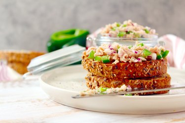 Tuna sandwich with relish and wheat bread on white plate