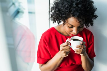 A woman drinking coffee as a natural remedy for constipation
