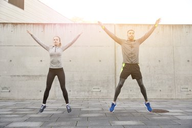 man and woman doing star jumps in front of a concrete wall