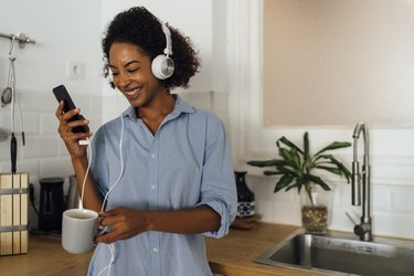 Woman with headphones, using smartphone and drinking coffee for breakfast in her kitchen