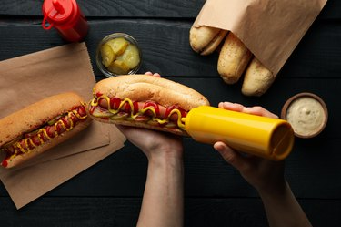 Person squeezes sauce on hot dog on wooden background, top view