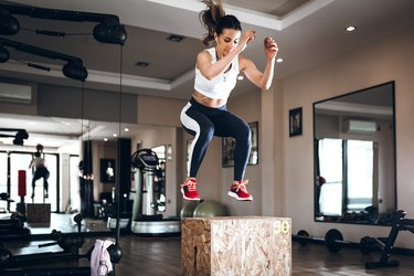 Woman doing box jumps in a gym