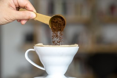 Hand Holding Spoon Of Instant Coffee Over Cup