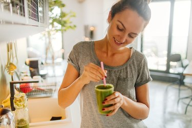 woman holding green smoothie in kitchen