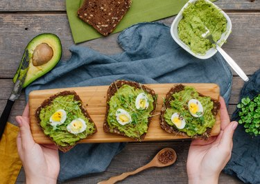Female hands holding homemade sandwiches with avokado, quail eggs and radish sprouts