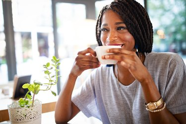Beautiful young african woman enjoying a cup of coffee