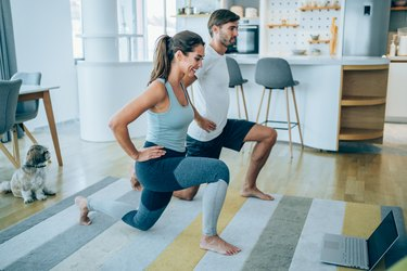 caucasian man and woman doing lunges at home in front of a computer