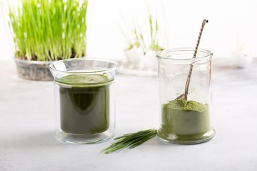 Wheatgrass shot. Organic green drink, wheatgrass powder and wheat sprouts  on white. Green superfood, micro greens, healthy eating  and detox concept.