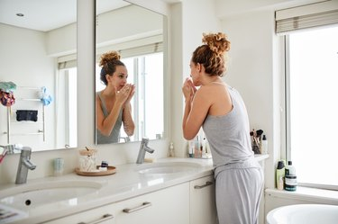 A woman checking how her keto breath smells in the bathroom