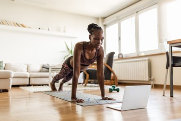 black woman doing push-ups in her living room at home