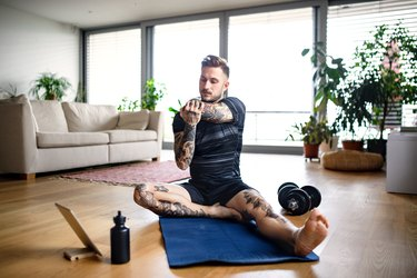 man with a flexibility fitness goal stretching in living room with a tablet, water bottle and dumbbells