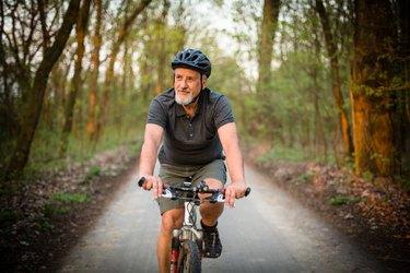 man wearing helmet biking outdoors for arthritis prevention