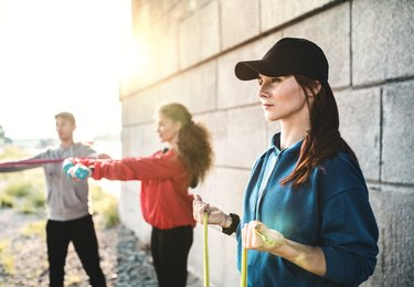 three people outside exercising with resistance bands and weights