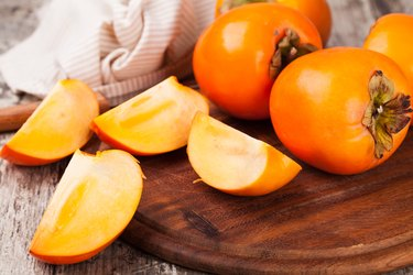 persimmon fruits, whole and sliced, on wooden board