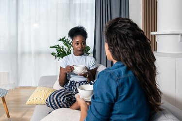 Two young people assigned female at birth best friends sitting on the sofa drinking tea and talking