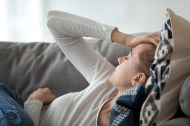 young woman lying on the couch and feeling tired because of chronic inflammation