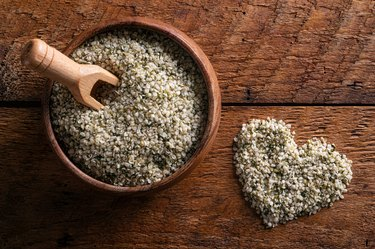 hemp heart seeds in a plate and spoon on a wooden background