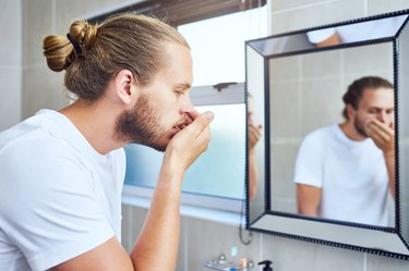 man in his bathroom at home checking his bad morning breath